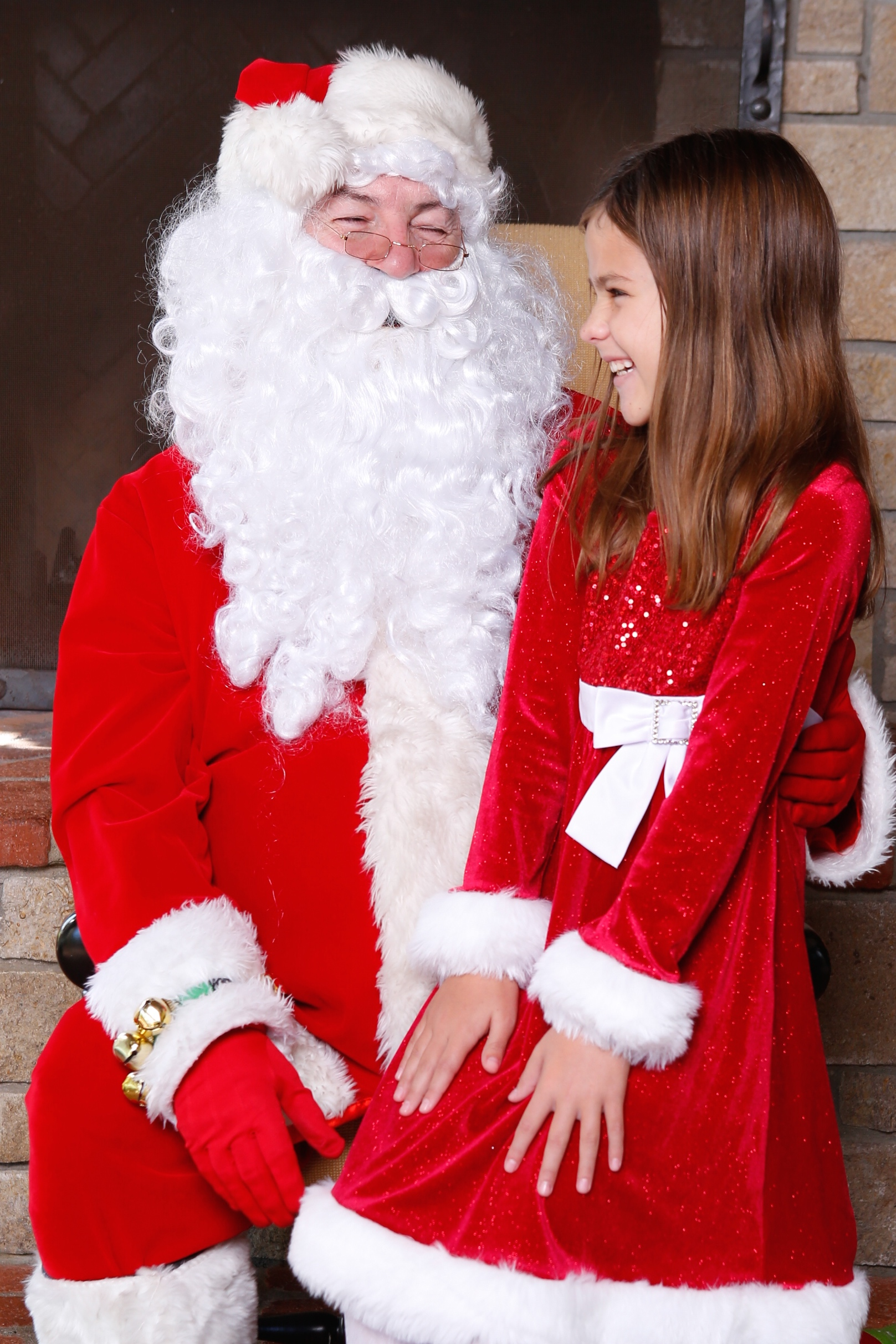 Smiling girl in red dress with Santa.